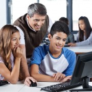 Happy mature teacher and students using desktop PC in classroom