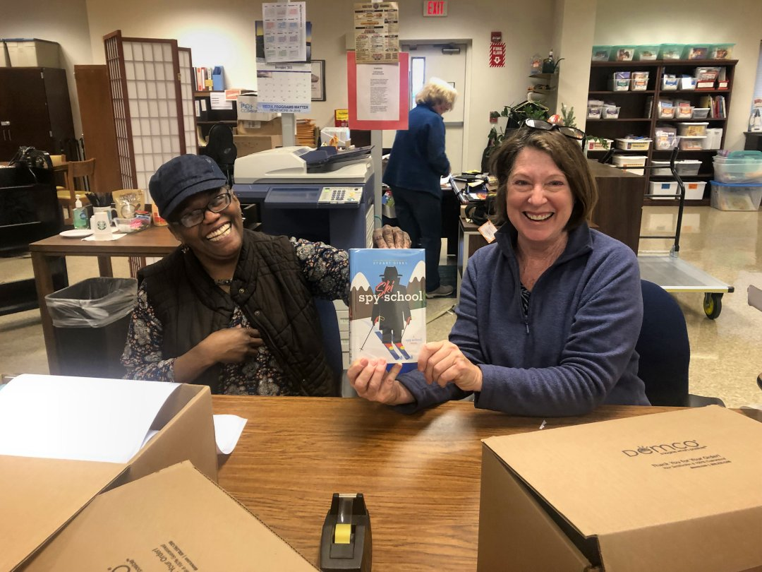 Volunteers Yvette Myers from Winston Salem Forsyth County Schools and Kay McKnight process books for distribution to local libraries