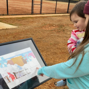 "Kellie and Sirena read ""A Snowy Day"", the winter book on the story walk trail at the Davie County Community Park"